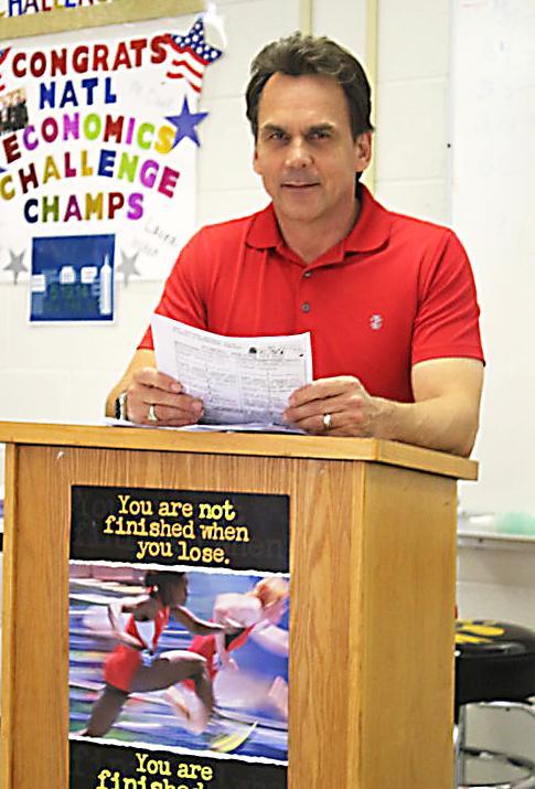 AP Economics teacher Michael Clark looking over the day's economic challenge for his students.