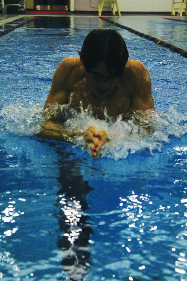 Senior Captain Andrew Weiner finishes a lap of breathstroke before the meet against Lamar High School