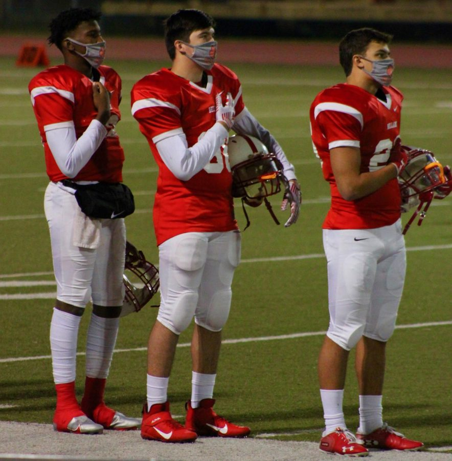 Varsity football players stand for the national anthem before a game agains Heights High School.