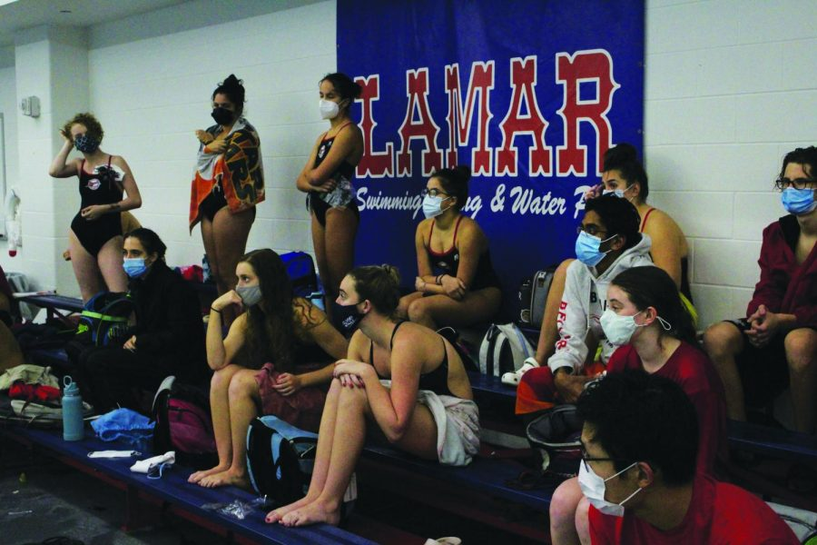 Swimmers watch from the bleachers as their teammates swim the 100 freestyle against Lamar High School