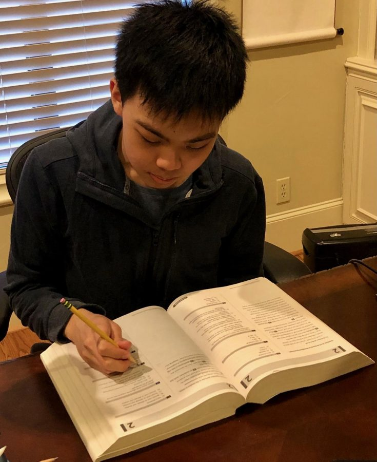 "Christopher Ho uses an SAT book to prepare for the PSAT. To make up for online school giving fewer practice opportunities, he took advantage of the recent power outages and got some practice in. ""I did a bunch of stuff I would have never found the resolve to do in the past because I would become distracted on YouTube,"" said Ho."