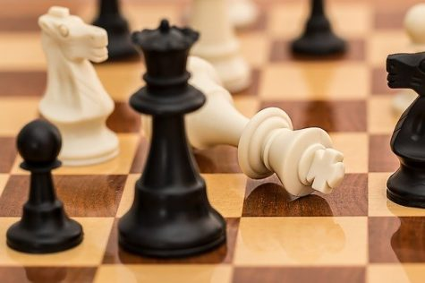The king falls in defeat as the opponent puts the chess pawn in check -- a game-winning move.