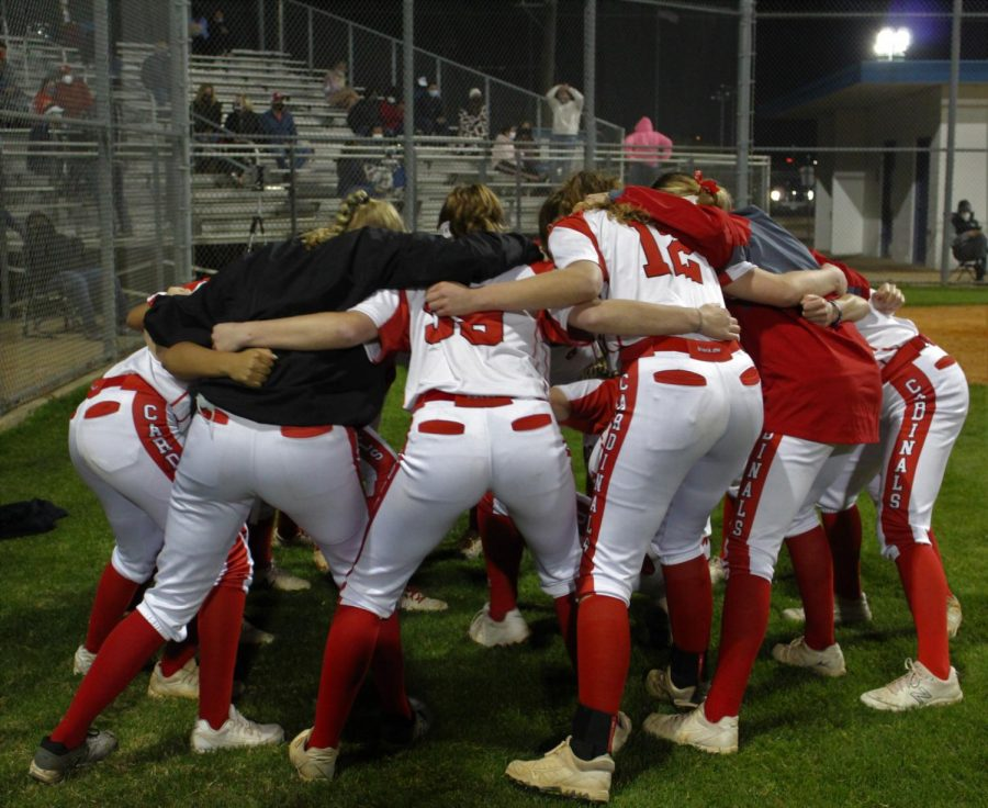 The varsity softball team huddles on the field before their game against rival school Lamar at Delmar Stadium on Mar. 2.