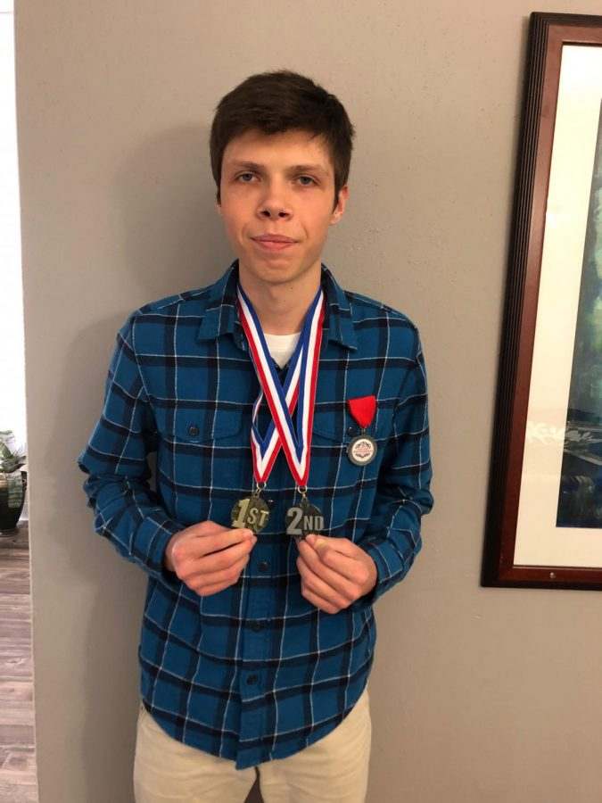Sophomore Davud Suvalic holds his two medals from the 2021 Houstonfest and Texas State German competitions. The competitions were held virtually this year,  but Suvalic still managed to place high.