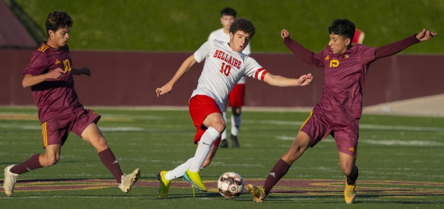 Senior and co-captain Jake Loor dribbles through two defenders during a preseason game against Deer Park. Loor won the 18-6A Most Valuable Player Award.