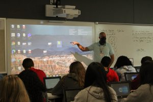Coach Brady Mayo teaches his fifth period class, Business Law. Students follow along on their personal computers.
