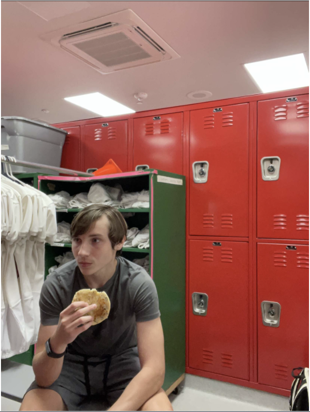 Sophomore Austin Schmidt eats a cold Eggo waffle in the boys locker room before school starts. During the first week of school, Schmidt adapted to eating breakfast in the locker room.